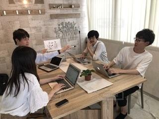 ラップトップ コンピューターを使用してテーブルに座っている人々 のグループの写真・画像素材[1323133]