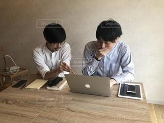 ラップトップを使用してテーブルに座っている人々 のグループの写真・画像素材[1323144]