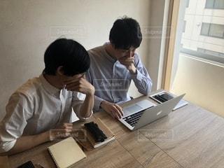 ラップトップ コンピューターを使用してテーブルに座っている男の人の写真・画像素材[1323155]