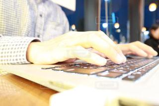 ラップトップ コンピューターを使用してテーブルに座っている人の写真・画像素材[1537095]