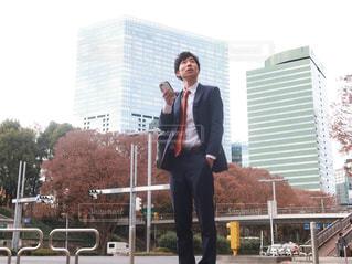 建物の前に立っているスーツの男の写真・画像素材[1666436]