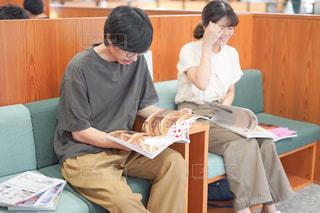 本を見てテーブルに座っている人々のグループの写真・画像素材[2493301]