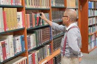 本棚の前に立っている男の写真・画像素材[2509300]