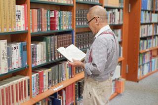 本棚の前に立っている人の写真・画像素材[2509303]