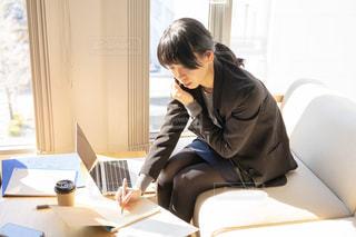 ラップトップを使ってテーブルに座っている人の写真・画像素材[2995182]