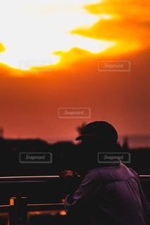 夕焼けの前に座っている人の写真・画像素材[2433266]