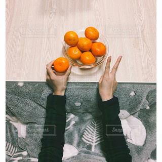 テーブルの上のオレンジのボールを保持している人の写真・画像素材[913699]
