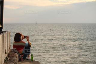 水の体の前に立っている人の写真・画像素材[857265]