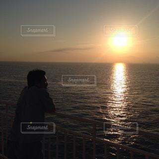 水の体の横に立っている人の写真・画像素材[1276936]