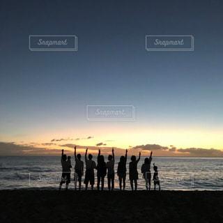 水の体の横に立っている人のグループの写真・画像素材[1703371]