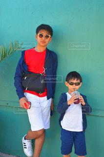 子の隣に立っている少年の写真・画像素材[1704036]