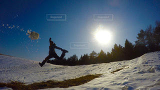 雪の空気中のジャンプ男覆われた斜面の写真・画像素材[1714653]