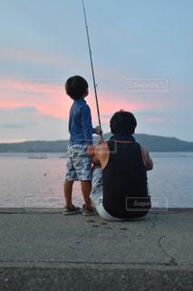 水の体の前で凧を飛ばす若い少年の写真・画像素材[2137921]