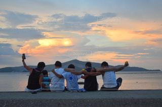 ビーチに座っている人々のグループの写真・画像素材[2137925]