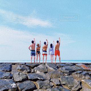 岩の多いビーチに立つ人々のグループの写真・画像素材[2374545]