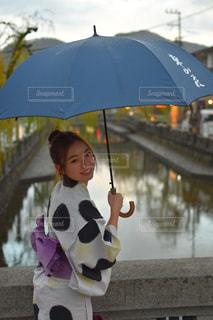 傘を持って雨の中に立っている小さな女の子の写真・画像素材[2812026]