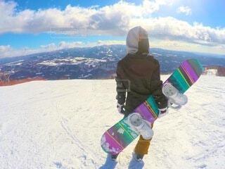 雪に覆われた山の下にスノーボードに乗っている男の写真・画像素材[4050704]