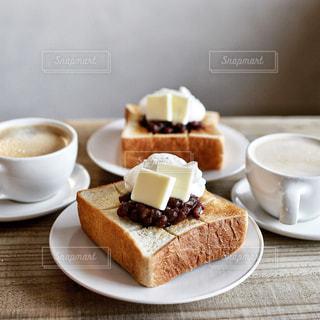 コーヒー カップの横にある皿の上のケーキの一部の写真・画像素材[1146836]