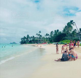 水の体の近くのビーチの人々 のグループの写真・画像素材[883612]