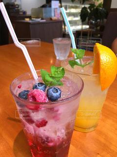 コーヒー カップの横にあるオレンジ ジュースのガラスの写真・画像素材[930705]