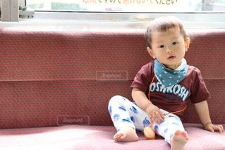 電車のイスに座っている赤ちゃんの写真・画像素材[1016839]