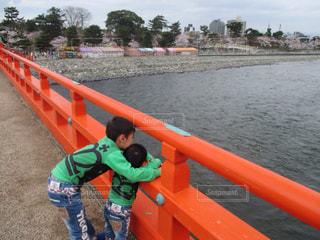 水の体の横に立っている小さな男の子の写真・画像素材[818779]