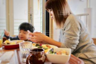 食事のテーブルに座っている女性の写真・画像素材[1173664]
