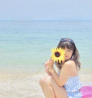 水の体の近くのビーチに座っている人の写真・画像素材[1261127]
