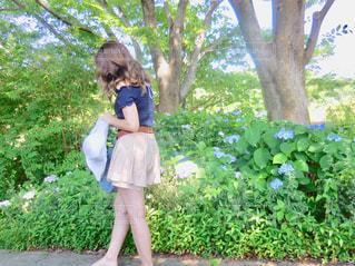 木の隣に立っている女の子の写真・画像素材[1267570]
