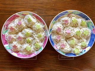 木製テーブルの上の皿の上に食べ物のボウルの写真・画像素材[1290170]