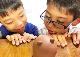 近くのテーブルに座っている小さな子供のアップの写真・画像素材[1321792]