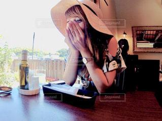 テーブルの上に座っている女性の写真・画像素材[1372940]
