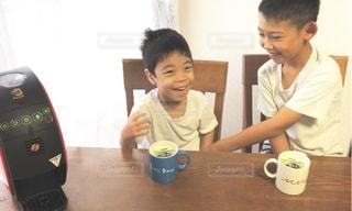 テーブルに座って若い男の子の写真・画像素材[1453671]