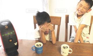 テーブルの上に座って若い男の子の写真・画像素材[1453674]