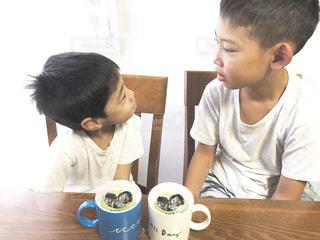 テーブルに座って若い男の子の写真・画像素材[1453675]
