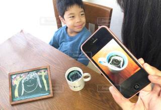 ラップトップを使用してテーブルに座っている少年の写真・画像素材[1455281]