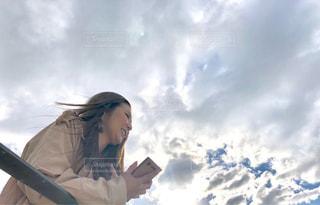 曇りの青い空に立っている女性の写真・画像素材[1585355]