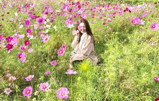 草にピンクの花の女性が立っています。の写真・画像素材[1585357]