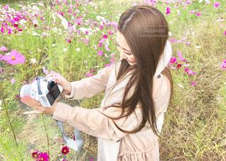 草の中に立っている間凧を保持している女性の写真・画像素材[1585358]