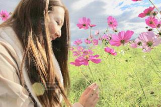 花の前に立っている女性の写真・画像素材[1585360]