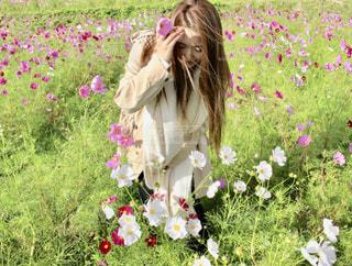 花の前に立っている人の写真・画像素材[1585364]