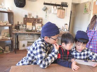 テーブルの上に座って若い男の子の写真・画像素材[1631504]