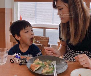 食事のテーブルに座っている女性の写真・画像素材[1640669]