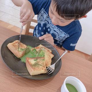食品のプレートをテーブルに座っている少年の写真・画像素材[1640674]