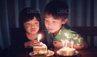 キャンドルの前のテーブルに座っている小さな男の子の写真・画像素材[1668367]