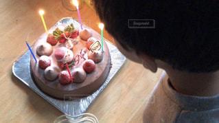 バースデー ケーキでテーブルに座っている人の写真・画像素材[1668369]