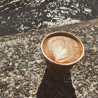 岩の上に座ってコーヒー カップの写真・画像素材[1851687]