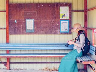 建物の前のベンチに座っている人の写真・画像素材[2122200]