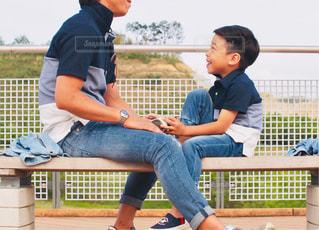 ベンチに座っている少年の写真・画像素材[2203714]