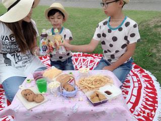 子ども,食べ物,飲み物,風景,公園,芝生,屋外,親子,帽子,草,ピクニック,人物,人,ボトル,お菓子,幼児,少年,ソフトド リンク,小岩井純水果汁